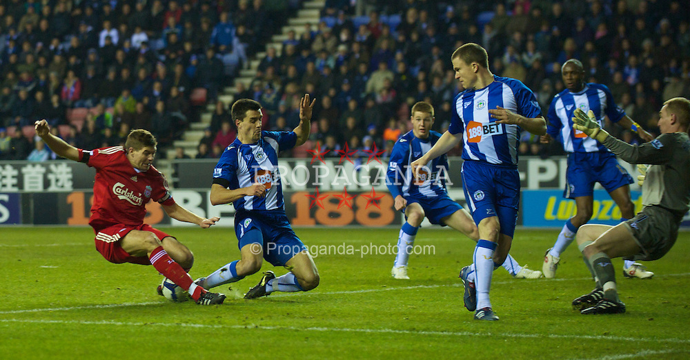 WIGAN, ENGLAND - Monday, March 8, 2010: Liverpool's captain Steven Gerrard MBE fluffs his shot under pressure from Wigan Athletic's Paul Scharner during the Premiership match at the DW Stadium. (Photo by David Rawcliffe/Propaganda)