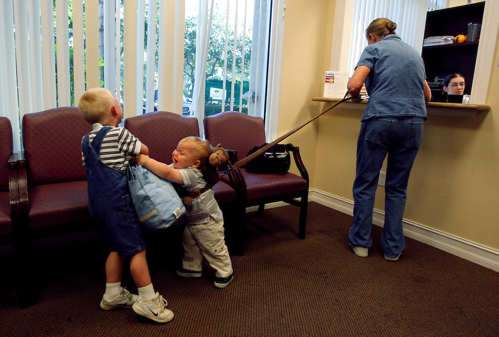 "Caleb Huth, 1, center, and brother Eran, 4, left, wrestle in the doctor's office waiting room while their great-`grandmother Katherine Smith schedules their next visit. After all of the doctor appointments for family, Smith doesn't have much money left over for her kids. ""I don't have the money to do all the things they want to do,"" Smith said. Greg Kahn/Staff"