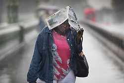 © Licensed to London News Pictures. 29/05/2018. London, UK. A woman shelters under a newspaper as she walks across  Westminster Bridge just as thunderstorms bring heavy rain to the capital.  Photo credit: Peter Macdiarmid/LNP