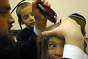 In Stamford Hill, London, United Kingdom on the 3rd birthday of a Orthodox Jewish boy he has his first ever hair cut leaving his peyos (sideburns) to grow. Here his father carefully shaves his head watched closely by his family. He will now begin to learn the Torah.
