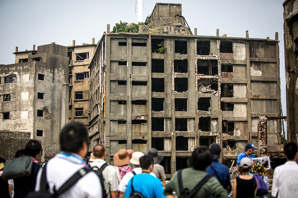 """NAGASAKI, JAPAN - AUGUST 8: Tourists visit a part of Hashima Island, commonly known as Gunkanjima or """"Battleship Island"""" in Nagasaki Prefecture, southern Japan on August 8, 2017. The island was a coal mining facility until its closure in 1974 is a symbol of the rapid industrialization of Japan, a reminder of its dark history as a site of forced labor during the Second World War. The island now is recognized as UNESCO's World Heritage sites of Japan's Meiji Industrial Revolution. (Photo: Richard Atrero de Guzman/NURPhoto)"""