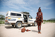 A traditional Himba woman stands next to a modern vehicle in the Kaokoland area of Northwestern Namibia, Africa.