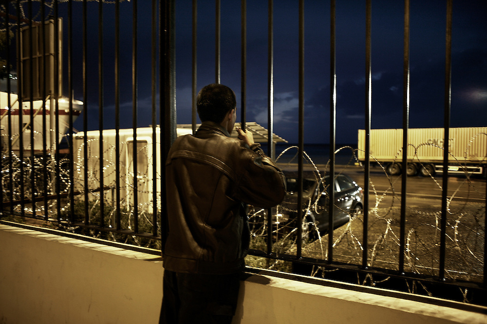 A young immigrant at Patras harbor is watching the trucks and waits for a chance to sneak in...Many illegal immigrants still stay at Patras trying to find a way to go to Italy and other European countries. The situation in Greece, has become rough due to police violence, asylum granted with dropper, human rights violations, denial about the rights of migrants on their arrival. UNHCR has expressed its concern about the situation, the immigrants seem more optimistic after the change of Greek government but no one really wants to stay in the country for long.