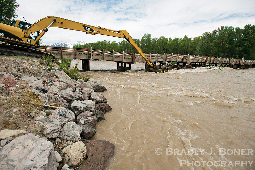Crews from Teton County Road and Levee clear debris from support pillars on Cattleman's Bridge on Friday afternoon. High spring runoff damaged one of the pillars, dropping the deck between two and three feet, which closed the bridge indefinitely.