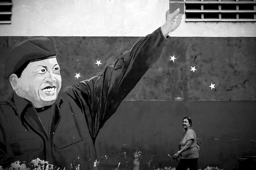 A woman passes a mural of Venezuelan President, Hugo Chavez, in Catia, a large slum in Caracas, Venezuela. Homicide rates have quadrupled since Chavez began his presidency in 1999. His critics blame the crime on a corrupt judicial system. Over 90 percent of violent crimes go unsolved in Venezuela.
