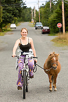 A young girl and her Shetland pony go for a stroll along the quiet streets of Sointula, a once utopian finnish community, on Malcolm Island.  Sointula, Malcolm Island, British Columbia, Canada.