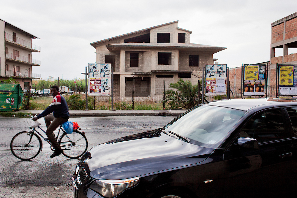 Rosarno, Italy - 1 September, 2012: An immigrant rides his bike in front of an unfinished home and a BMW car parked on the sidewalk of a bar in Rosarno, Italy, a mafia stronghold on September 1st, 2012.  The unfinished concrete buildings, which are very common throughout Calabria, are the result of the inability to go beyond the merely useful, creating functionality without regard for form.<br /> <br /> Rosarno is an agricultural area best known for the violent race riots that erupted here in January 2010. and for being a hotbed of the 'Ndrangheta, a Mafia-type criminal organisation based in Calabria. The local 'Ndrangheta dominates the fruit and vegetable businesses in the area, according to Francesco Forgione, a former head of Italy's parliamentary Antimafia Commission. In December 2008, the entire town council was dissolved on orders from the central government and replaced by a prefectoral commissioner because it had been infiltrated by 'Ndrangheta members and their known associates.<br /> <br /> Calabria is one of the poorest Italian regions which suffers from lack of basic services (hospitals without proper equipment, irregular electricity and water), the product of disparate political interests vying for power. The region is dominated by the 'Ndrangheta (pronounced en-Drang-get-A), which authorities say is the most powerful in Italy because it is the welthiest and best organized.<br /> <br /> The region today has nearly 20 percent unemployment, 40 percent youth unemployment and among the lowest female unemployment and broadband Internet levels in Italy. Business suffer since poor infrastructure drives up transport costs.<br /> <br /> Last summer the European Union's anti-fraud office demanded that Italy redirect 380 million euros in structural funding away from the A3 Salerno - Reggio Calabria highway after finding widespread evidence of corruption in the bidding processes.