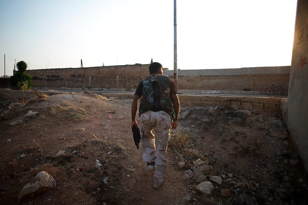 August 09, 2012 - Marea, Aleppo, Syria: A Free Syria Army (FSA) fighter walks towards a rebel checkpoint in an access road to Aleppo...The Syrian army and the FSA have in the past week exchanged heavy fire in a battle for the control of Syria's economic capital, Aleppo. (Paulo Nunes dos Santos/Polaris)