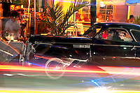 Antique car parked in front of restaurant in famous Ocean Drive in Miami Beach. Ocean Drive is a very colorful place with neon lights and activity.