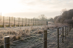 Harefield, UK. 21 January, 2020. The sun rises behind fencing and a security camera on land in the Colne Valley designated for the HS2 high-speed rail link.