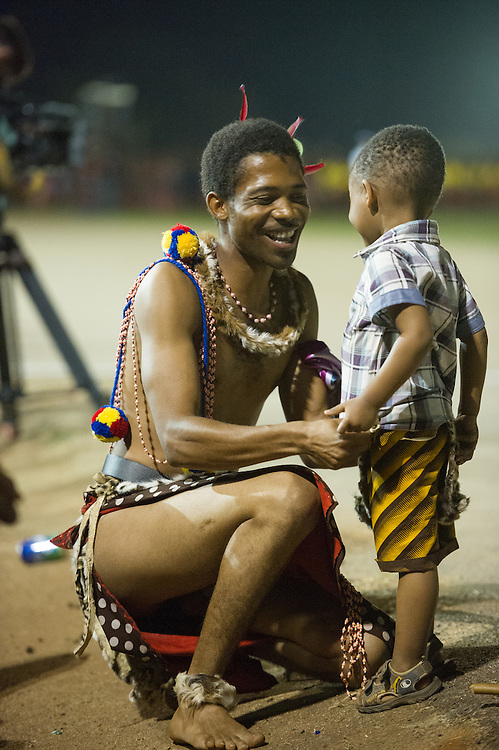 Ludzidzini, Swaziland, Africa - Annual Umhlanga, or reed dance ceremony, in which up to 100,000 young Swazi women gather to celebrate their virginity and honor the queen mother during the 8 day long event.<br /> Warrior with child