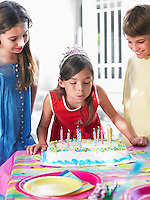 Girl (8-12) blowing out birthday candles