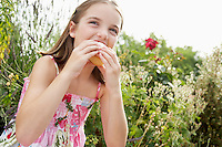Young girl sitting in meadow eating cupcake close up