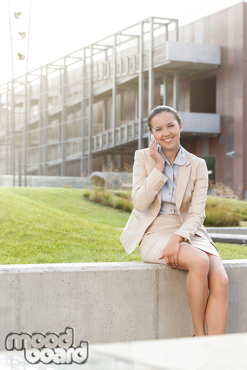 Happy young businesswoman using mobile phone while sitting on wall against office building