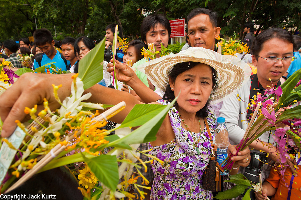 "15 JULY 2011 - PHRA PHUTTHABAT, SARABURI, THAILAND:   A woman presents flowers to a float carrying a robed statue of the Buddha during the Tak Bat Dok Mai at Wat Phra Phutthabat in Saraburi province of Thailand, Friday, July 15. Wat Phra Phutthabat in Phra Phutthabat, Saraburi, Thailand, is famous for the way it marks the beginning of Vassa, the three-month annual retreat observed by Theravada monks and nuns. The temple is highly revered in Thailand because it houses a footstep of the Buddha. On the first day of Vassa (or Buddhist Lent) people come to the temple to ""make merit"" and present the monks there with dancing lady ginger flowers, which only bloom in the weeks leading up Vassa. They also present monks with candles and wash their feet. During Vassa, monks and nuns remain inside monasteries and temple grounds, devoting their time to intensive meditation and study. Laypeople support the monastic sangha by bringing food, candles and other offerings to temples. Laypeople also often observe Vassa by giving up something, such as smoking or eating meat. For this reason, westerners sometimes call Vassa the ""Buddhist Lent."" The tradition of Vassa began during the life of the Buddha. Most of the time, the first Buddhist monks who followed the Buddha did not stay in one place, but walked from village to village to teach. They begged for their food and often slept outdoors, sheltered only by trees. But during India's summer rainy season living as homeless ascetics became difficult. So, groups of monks would find a place to stay together until the rain stopped, forming a temporary community. Wealthy laypeople sometimes sheltered monks on their estates. Eventually a few of these patrons built permanent houses for monks, which amounted to an early form of monastery.   PHOTO BY JACK KURTZ"