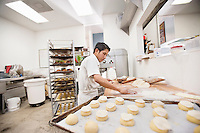 Young baker making dough in bakery kitchen
