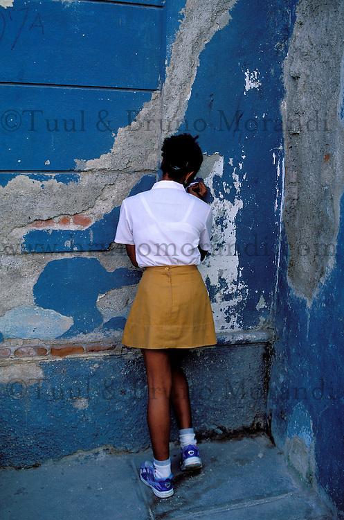 Cuba, Santiago de Cuba, Ecoliere qui corrige ses devoirs dans la rue //  Cuba. Santiago de Cuba, District of Tivoli, young student