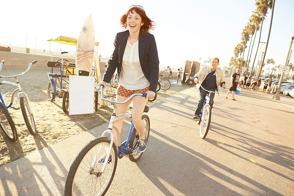 Lifestyle image of girl cycling along sunny beach in Southern California and having fun