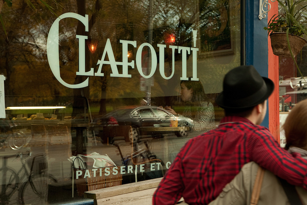 A couple walking by Clafouti, a patisserie on Toronto's trendy Queen Street West.
