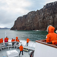 Guests gather on the bow of the National Geographic Explorer as it navigates into the caldera of Deception Island in Antarctica.