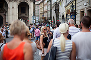 Crowds of Prague imhabitants and tourists at the end of Cherles Bridge heading into Karlova Street connecting the Old Town Square with Charles Bridge.