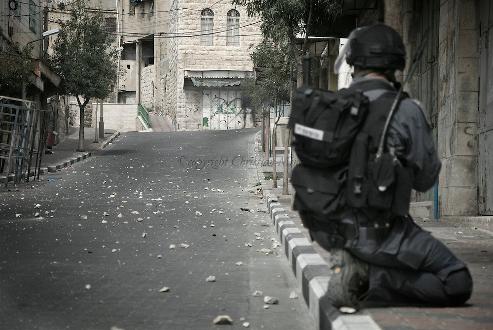 An Israeli soldier takes position during clashes in the West Bank city of Hebron, Monday, Feb. 22, 2010. Palestinians clashed with Israeli troops in Hebron amid outrage over Israel's plan to restore two flashpoint Jewish holy sites in the occupied territory.