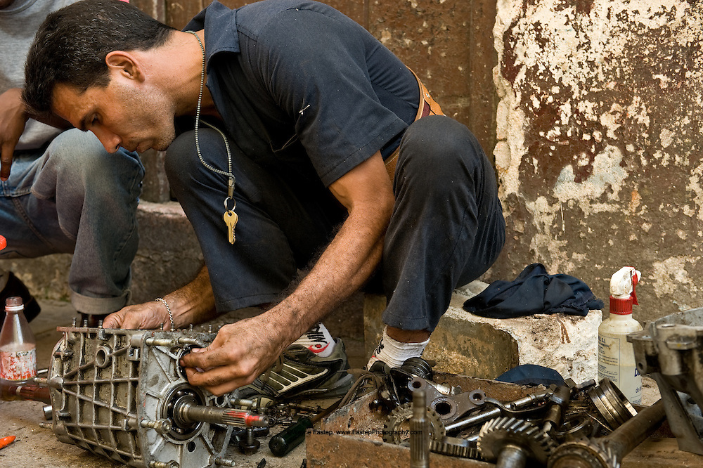 Lazaro Ingian, auto mechanic, repairing a transmission on the corner of Amistad and San Miguel in Central Havana.