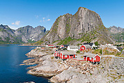 Red rorbus perch on stilts in Hamnøy  fishing village along the shore of Reinefjord, Lofoten archipelago, Nordland county, Norway.