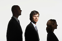 Businesspeople standing in row in height order middle man facing camera in spotlight