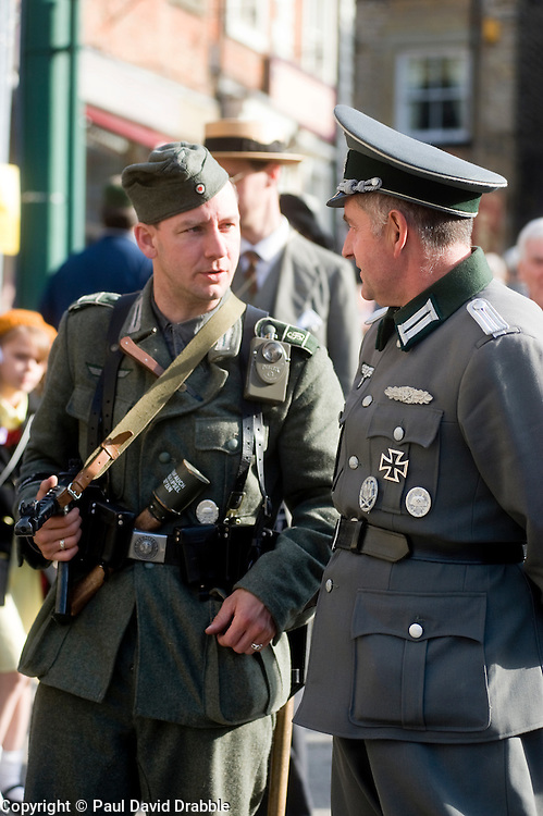 "Two re-enactors portraying a German soldier with MP40 submachine gun and ""potato Masher"" stick grenade (left) chats to a German Officer chat on the streets of Pickering during the 1940s war weekend October 2009 Image Copyright Paul David Drabble"