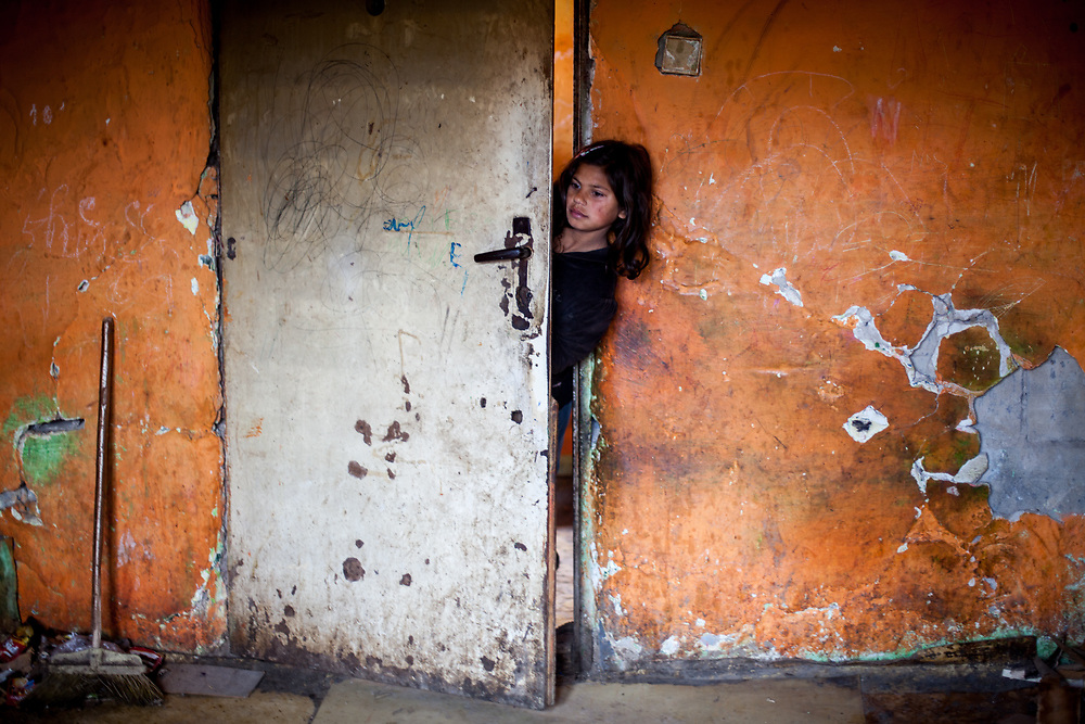 """A young girl is watching into the flat of Jan Ondic - 87 years of age who is one of the oldest inhabitants at the Roma settlement. He lives at the Roma part of the district """"Podsadek"""". The town of Stara Lubovna has a population of 16350, of whom 2 060 (13%) are of Roma origin. The majority of Roma live in the Podsadek district, where 980 (74%) out of 1330 inhabitants are Roma."""