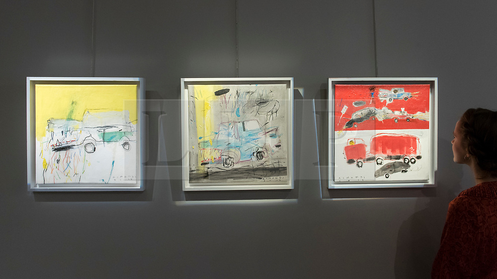 """© Licensed to London News Pictures. 20/11/2018. LONDON, UK.  A staff member views (L to R) """"Yellow Light"""", """"The Monster"""", """"Three Accidents"""", all 2018, all by Mohammed Al Mahdi.  Preview of """"Accumulation:  Legacy and Memory"""", an exhibition presented by Art Bahrain Across Borders during Bahrain Art Week.  Works from 11 emerging and established Bahraini artists is on display 20th to 26 November at Alon Zakaim Fine Art gallery in Mayfair.  Photo credit: Stephen Chung/LNP"""