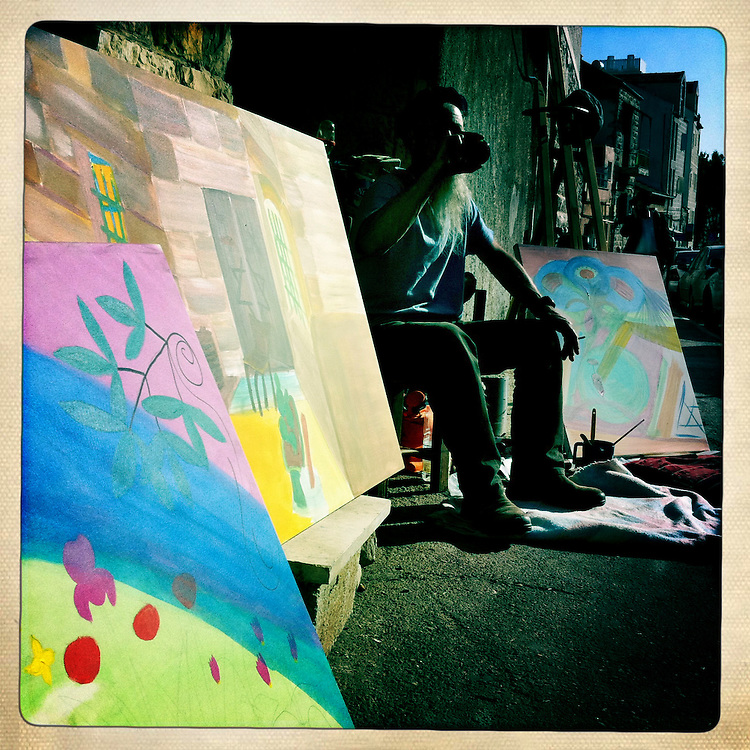 Eyal Shilo sits by his art in the afternoon sun in a residential neighborhood near Mechaneh Yehuda in Jerusalem, Israel