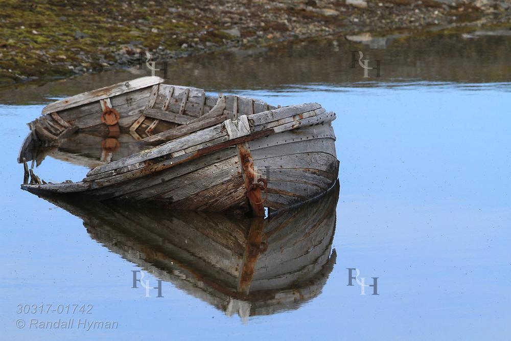 Dilapidated rowboat sits in pond near Ny-Alesund on Spitsbergen island; Svalbard, Norway.