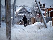 Passant laeuft durch eine winterliche Landschaft in einen Vorort der sibirischen Stadt Jakutsk. Jakutsk wurde 1632 gegruendet und feierte 2007 sein 375 jaehriges Bestehen. Jakutsk ist im Winter eine der kaeltesten Grossstaedte weltweit mit durchschnittlichen Winter Temperaturen von -40.9 Grad Celsius. Die Stadt ist nicht weit entfernt von Oimjakon, dem Kaeltepol der bewohnten Gebiete der Erde.<br /> <br /> Passerby walking through a Siberian winter landscape in a suburb of the city of Yakutsk. Yakutsk was founded in 1632 and celebrated 2007 the 375th anniversary - billboard announcing the celebration. Yakutsk is a city in the Russian Far East, located about 4 degrees (450 km) below the Arctic Circle. It is the capital of the Sakha (Yakutia) Republic (formerly the Yakut Autonomous Soviet Socialist Republic), Russia and a major port on the Lena River. Yakutsk is one of the coldest cities on earth, with winter temperatures averaging -40.9 degrees Celsius.