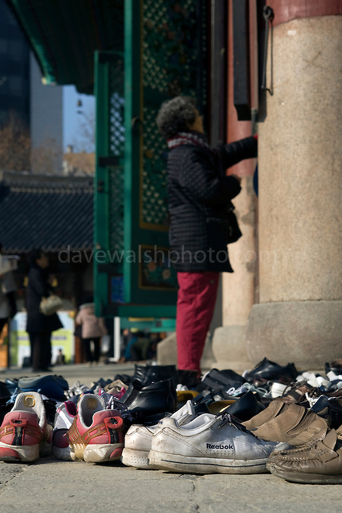 Woman praying, and shoes outside the Hall of the Great Hero or Daeung-jeon at Jogye-sa Buddhist Temple, Seoul, South Korea. Jogyesa is the main temple of the Jogye Order of Korean Buddhism, and has a important part in Seon Buddhism. Located in Gyeonji-dong, Jongno-gu within in the old city of Seoul.
