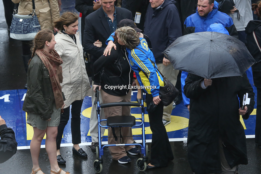April 14, 2014 - Boston, Massachusetts, USA - <br /> <br /> Boston Marathon Bombing Anniversary<br /> <br /> Hundreds gather at the Boston Marathon finish line in Boston, Massachusetts to mark the one year anniversary of the Boston Marathon Bombing. United States Vice President Joe Biden attended the event. Bombing Survivor Erika Brannock receives a hug from her mother Carol Downing as she crosses the finish line. Erika was injured by the first blast as she was at the finish line cheering her mother Carol Downing on.<br /> &copy;Exclusivepix