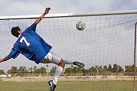 Soccer player scoring goal back view