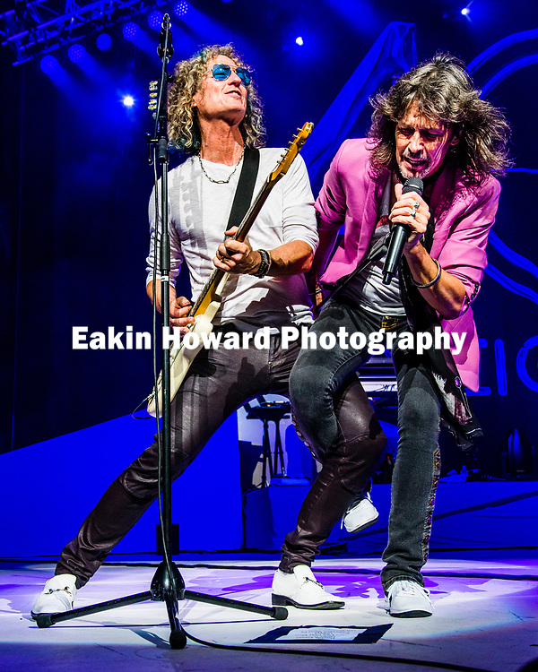 Foreigner's Kelly Hansen, on vocals, wraps his leg around Bruce Watson, on electric guitar, on the stage of the PNC Music Pavilion in Charlotte, NC on August 5, 2017. This concert was part of Foreigner's 40th Anniversary Tour.