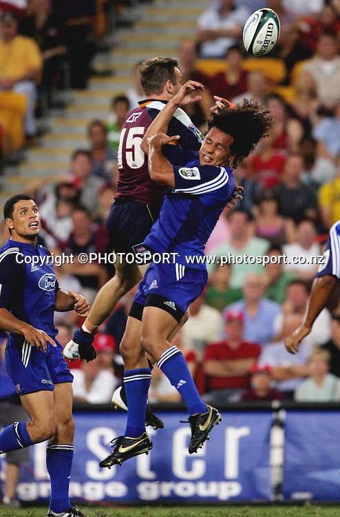 Reds fullback Chris Latham leaps high to beat Isakeli Nacewa to a midfield bomb during the 2006 Super 14 rugby union match between the Reds and the Auckland Blues at Suncorp Stadium, Brisbane, Australia, on Saturday 25 February, 2006.Blues defeated Reds 21-20. Photo: PHOTOSPORT