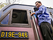 06 APRIL 2012 - HANOI, VIETNAM: The engineer climbs into the cab of the Hanoi to Hai Phong Express Train in Hanoi. The Hanoi to Hai Phong Express Train runs several times a day between Long Bien Station in Hanoi and the Hai Phong Station. Hanoi is the capital of Vietnam and Hai Phong is the 4th largest city in Vietnam. Hai Phong is the principal industrial port in the northern part of Vietnam. It was heavily bombed and mined during the American War (what Americans call the Vietnam War).   PHOTO BY JACK KURTZ