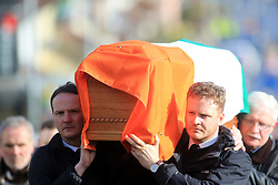 © London News Pictures. 21/03/2017. Derry, UK. Fiachra McGuinness andEmmet McGuinness carry the coffin of their father Martin McGuinness though the streets the Bogside area of Derry, Northern Ireland, 21 March 2017. Sinn Féin's Martin McGuinness, Northern Ireland's former deputy first minister died aged 66 early this morning. It is understood he had been suffering from a rare heart condition. The former IRA leader turned peacemaker worked at the heart of the power-sharing government following the 1998 Good Friday Agreement. He became deputy first minister in 2007, standing alongside Democratic Unionist Party leaders Ian Paisley, Peter Robinson and Arlene Foster.. Photo credit: LNP