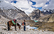 Our cook Juan, with horse, descends from Caracara Pass down into Alpamayo Valley, in Huascaran National Park (UNESCO World Heritage Site), Cordillera Blanca, Andes Mountains, Peru, South America. Above the turquoise Jancarurish Lake is the pyramidal peak of Nevado Alpamayo (19,511 ft or 5947 m) in the clouds. This is day 6 of 10 days trekking around Alpamayo (starting from Vaqueria).