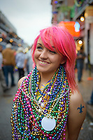 A young woman wearing lots of beads smiles on Bourbon Street during Mardi Gras in New Orleans, Louisiana.