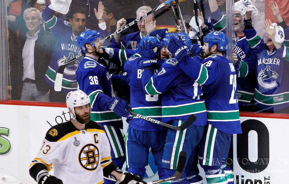June 1, 2011; Vancouver, BC, CANADA; Vancouver Canucks left wing Raffi Torres (middle) is mobbed by teammates after scoring the game winning goal as Boston Bruins defenseman Zdeno Chara (33) during the third period in game one of the 2011 Stanley Cup Finals at Rogers Arena. The Canucks won 1-0. Mandatory Credit: Jason O. Watson / US PRESSWIRE