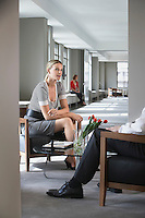 Businesswoman sitting talking to businessman in office