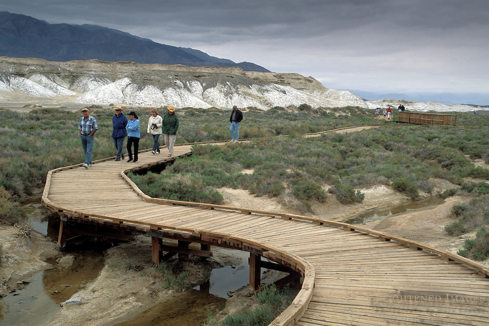 Tourists walking on wooden boardwalk nature trail path at Salt Creek, Death Valley National Park, California
