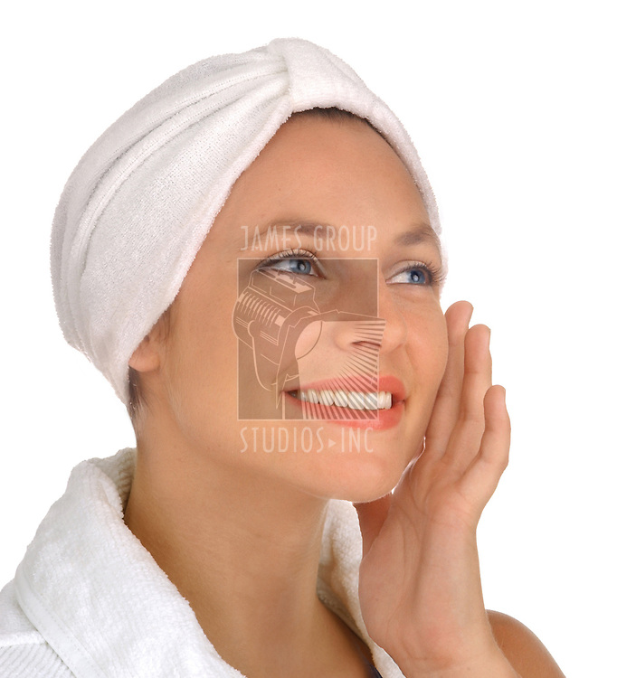 pretty woman holding hand against face wearing spa robe and turban