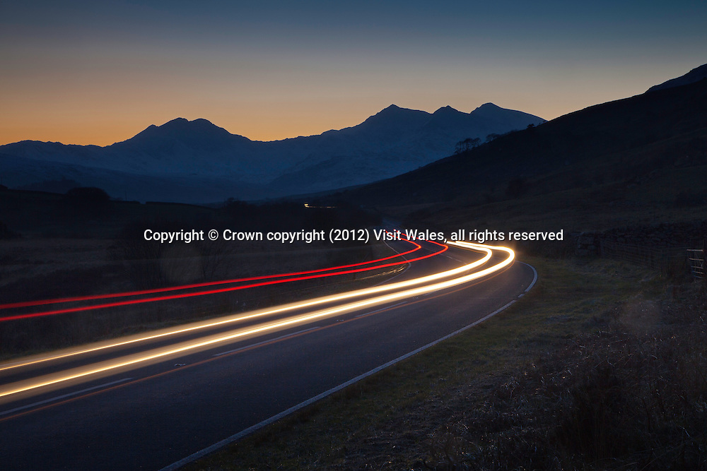 A4086 road with traffic trails at twilight and Snowdon Horseshoe in background<br /> Capel curig<br /> Conwy County<br /> North<br /> Road<br /> Transport