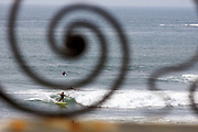 USA, Newport, RI - Surfers shown through iron work of Breakers Mansion gate on cliff walk.